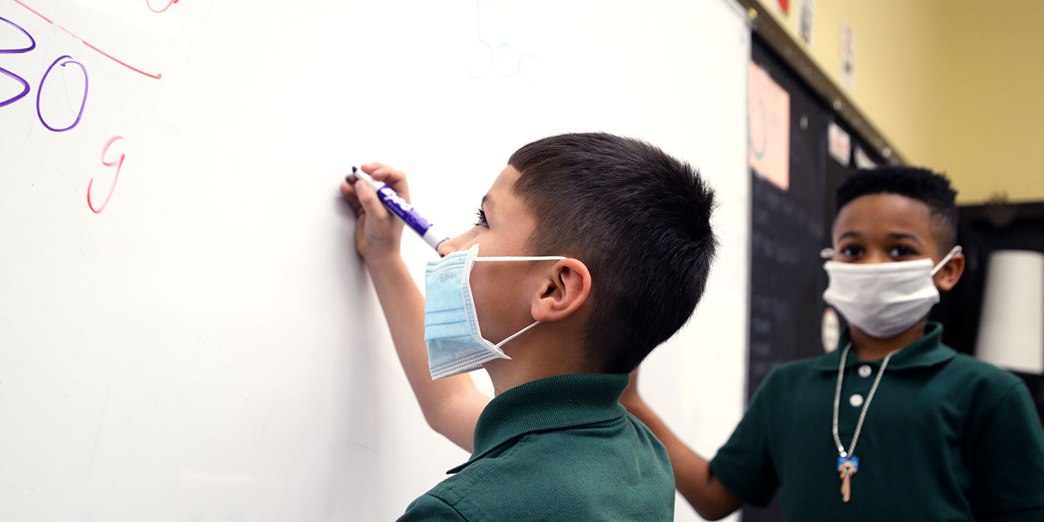 Students writing on white board at front of class.