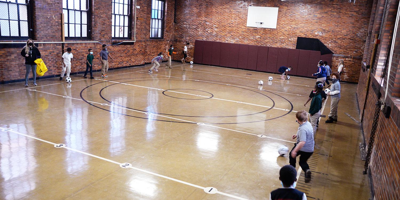 Students kicking soccer balls in school gym.