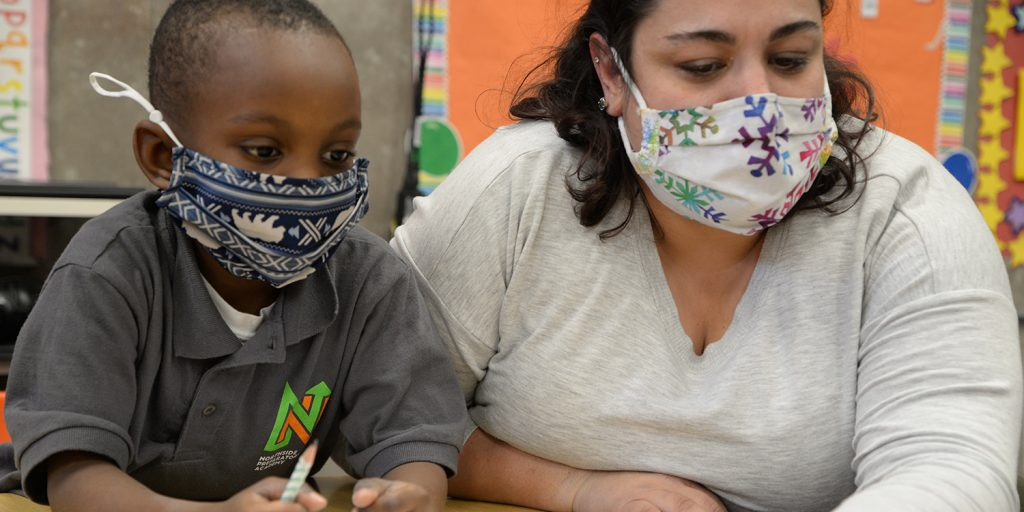 Masked kindergarten teacher and student at a desk and looking at a project.